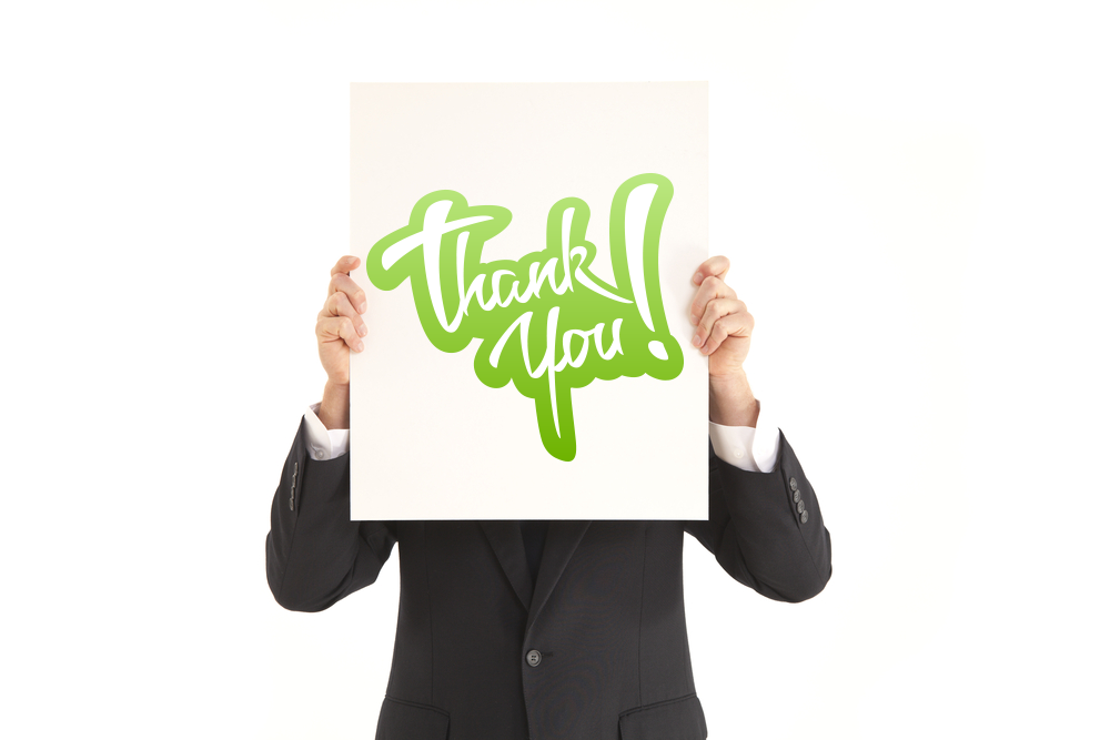 man in suit holding blank sign in front of face with Thank You